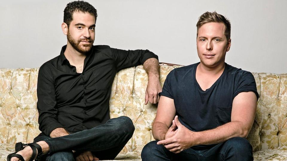 Deux hommes assis sur un divan.