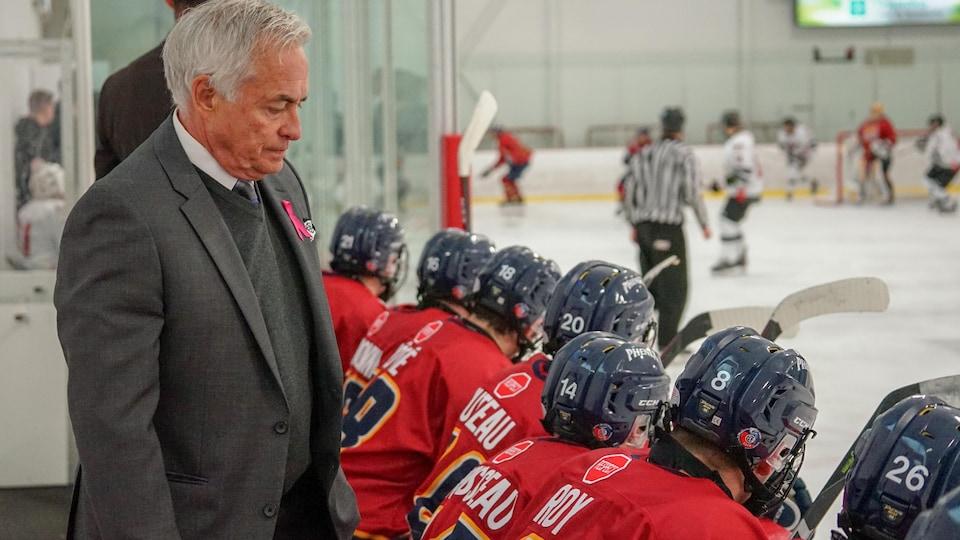 Un entraîneur derrière un banc de joueurs pendant un match