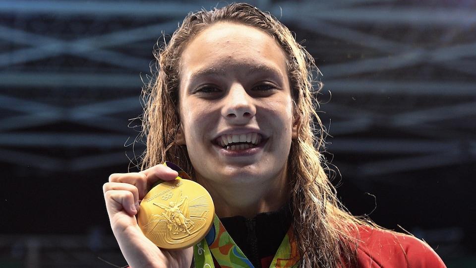 Penny Oleksiak montre sa médaille d'or aux photographes. Avec un record olympique en poche, elle a grimpé sur la plus haute marche du podium au 100 m libre.