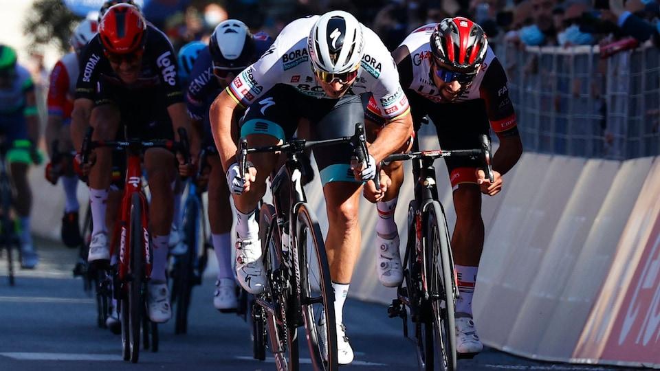 Un cycliste, en position de sprint, est pourchassé par ses rivaux.