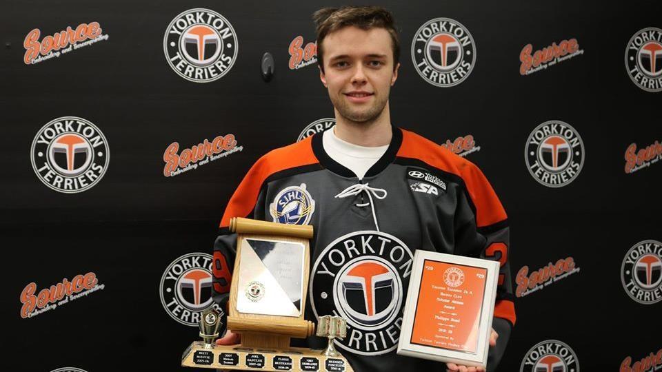 Philippe Bond pose avec son chandail en tenant une plaque et un trophée.