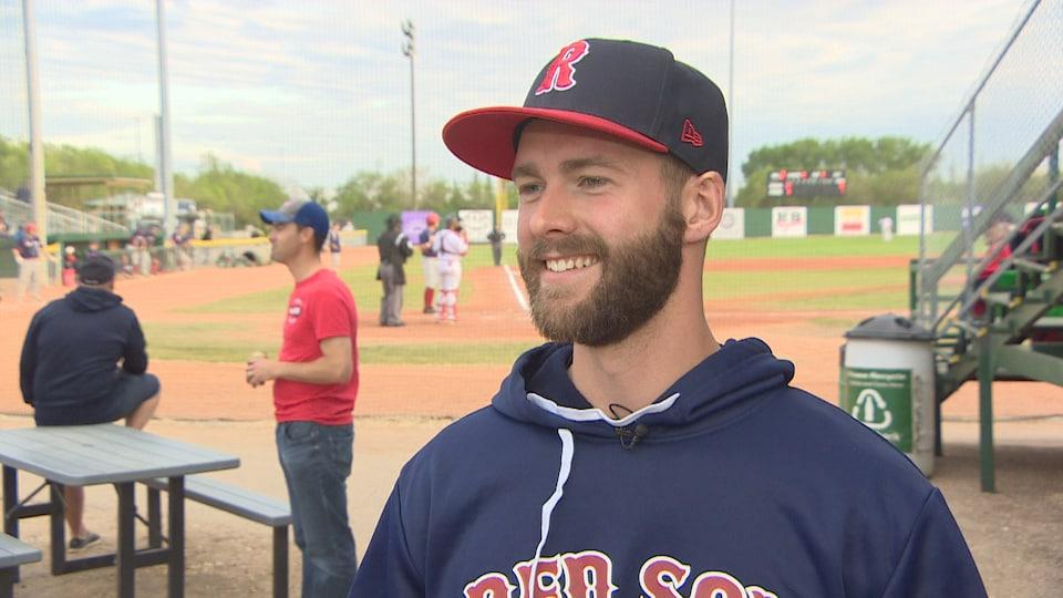Philippe Langlois tout sourire en entrevue près du terrain de baseball des Red Sox de Regina.