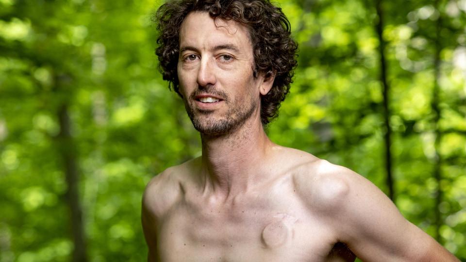Un homme aux cheveux brun bouclés prend la pose torse nu.
