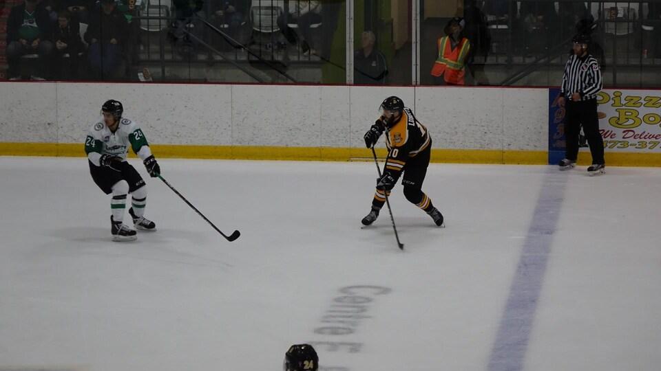Deux joueurs sont sur la patinoire près de la ligne bleue.
