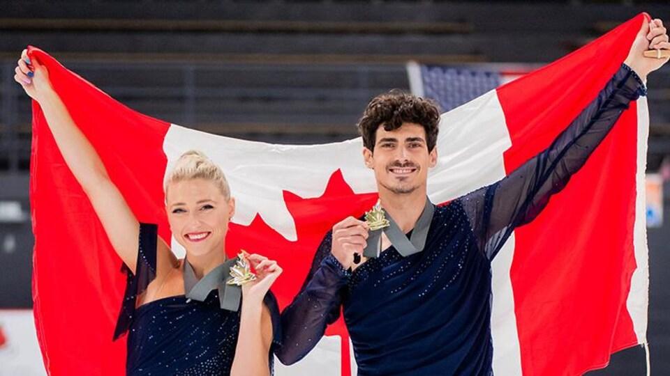 Le duo soulève derrière lui le drapeau canadien, avec médaille d'or en main.