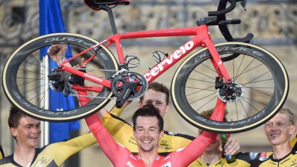Primoz Roglic soulève son vélo à bout de bras pour célébrer sa troisième victoire d'affilée au Tour d'Espagne.