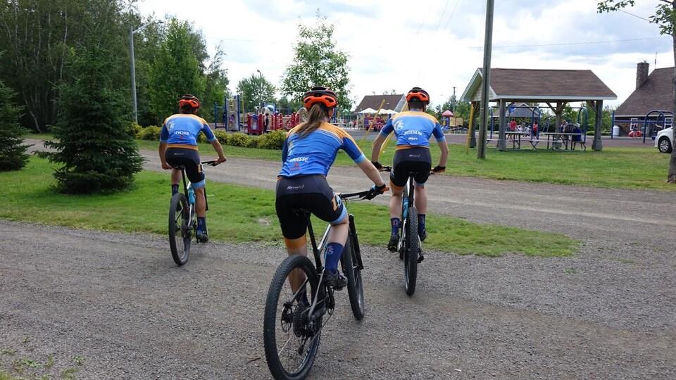 Trois jeunes habillés identiquement sur leur vélo de montagne.