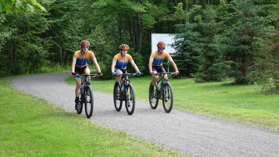 Trois cyclistes côte-à-côte sur le vélo de montagne.