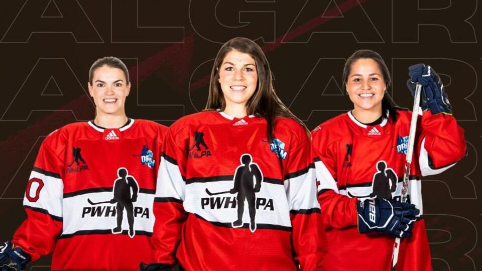 Trois joueuses souriantes portant le chandail de l'Association des joueuses professionnelles de hockey (PWHPA)
