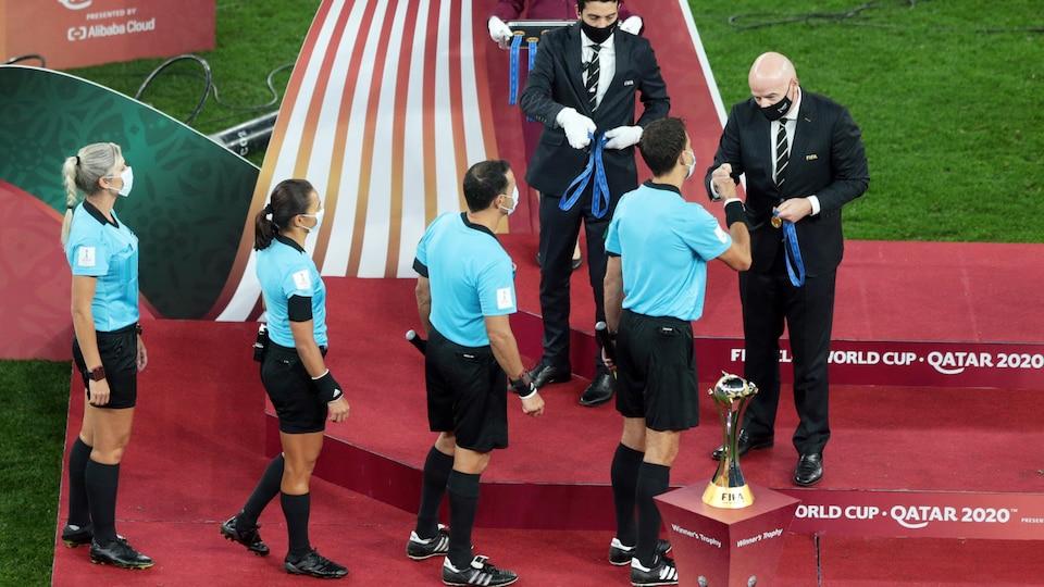 Gianni Infantino remet une médaille à quatre arbitres qui font la queue.