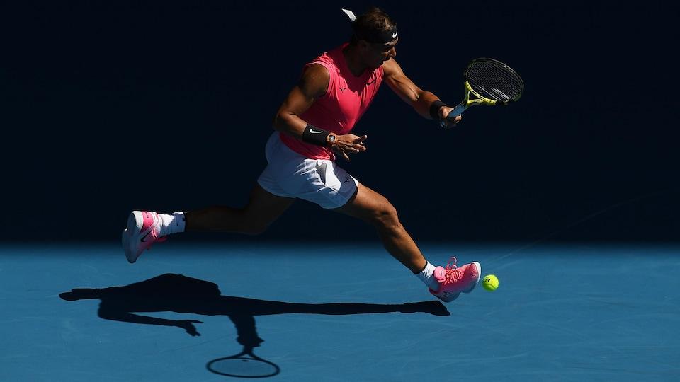 Rafael Nadal court pour frapper la balle de coup droit.