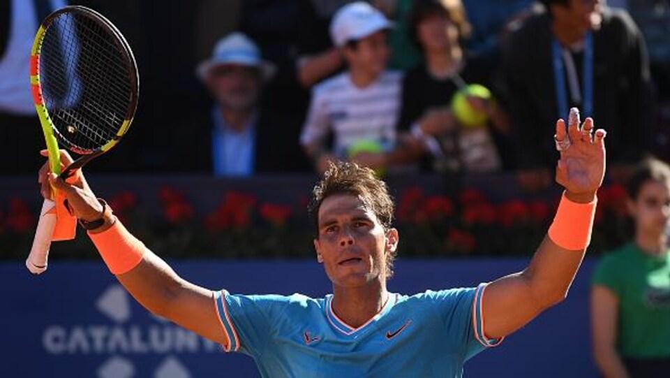 Il salue la foule après sa victoire.