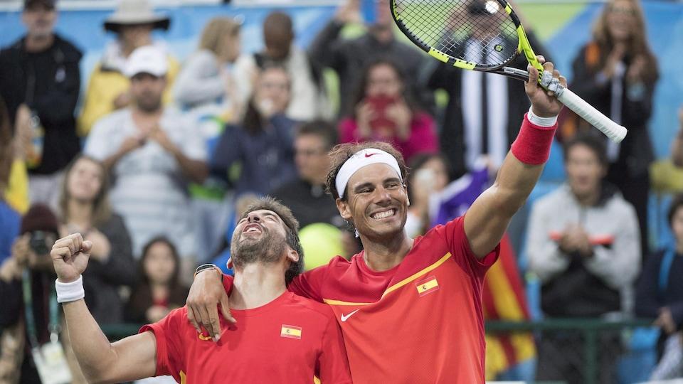 Rafael Nadal salue la foule avec sa raquette, tout en prenant son coéquipier Marc Lopez par l'épaule.