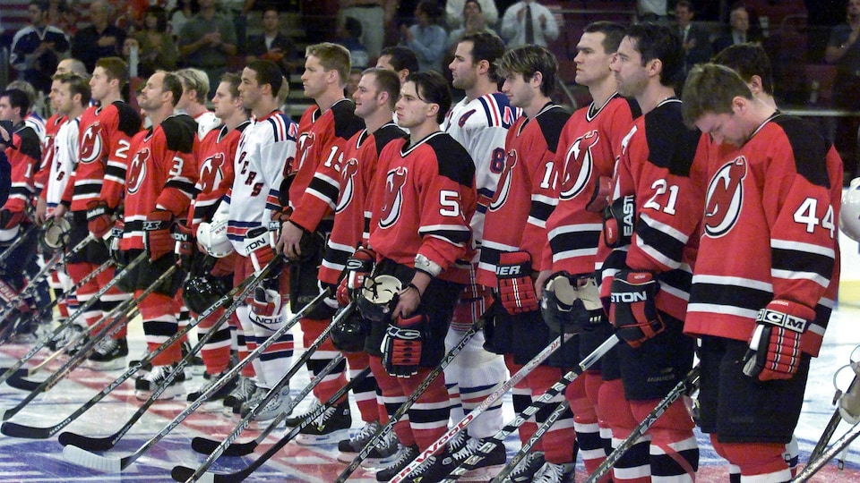 Les joueurs des deux équipes se tiennent côte à côte, solennellement.