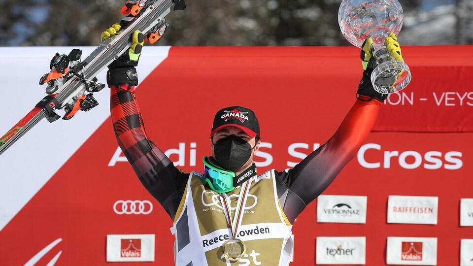 Un skieur tient ses skis dans une main et un trophée de l'autre.