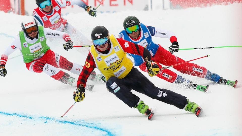 Il est devant trois autres skieurs.