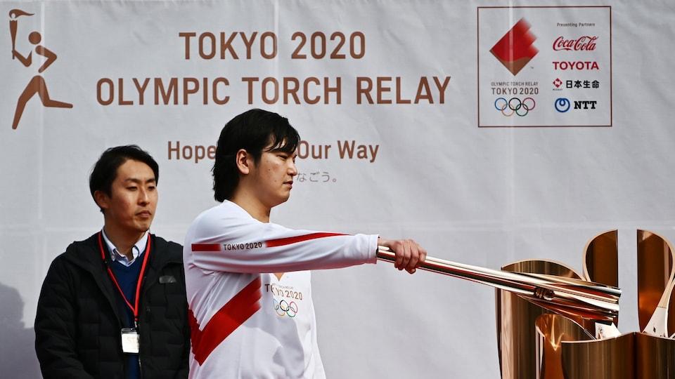 Une personne allume le flambeau lors d'une répétition du relais de la flamme des Jeux de 2020 à Tokyo.