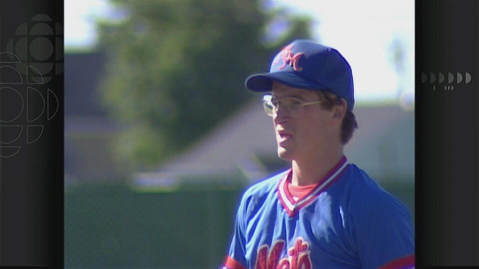 Homme avec des lunettes et une casquette de baseball.