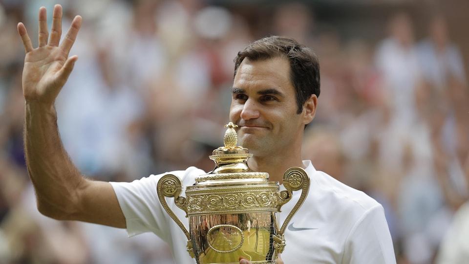 Il tient le trophée de Wimbledon dans la main gauche et salue la foule de la droite.