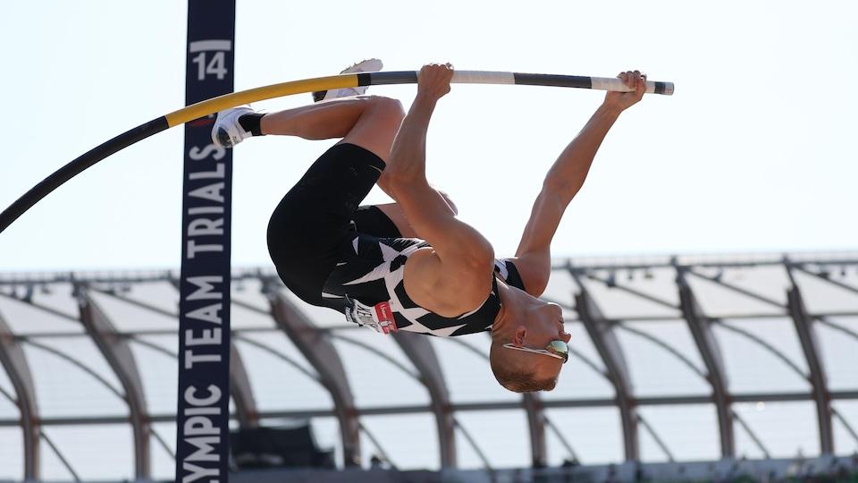 Un sauteur est accroché à sa perche, fortement pliée, il se retrouve la tête en bas lors d'une tentative de saut.