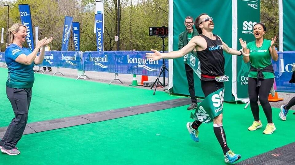 Un coureur vêtu de noir franchit le fil d'arrivée du marathon de Longueuil au premier rang en 2018.