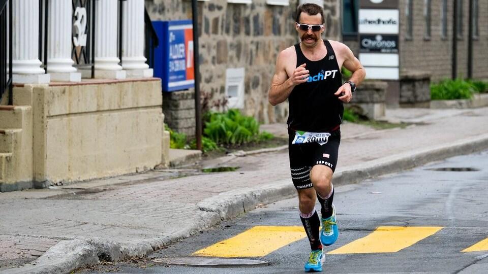 Un coureur vêtu de noir participe au marathon de Longueuil.