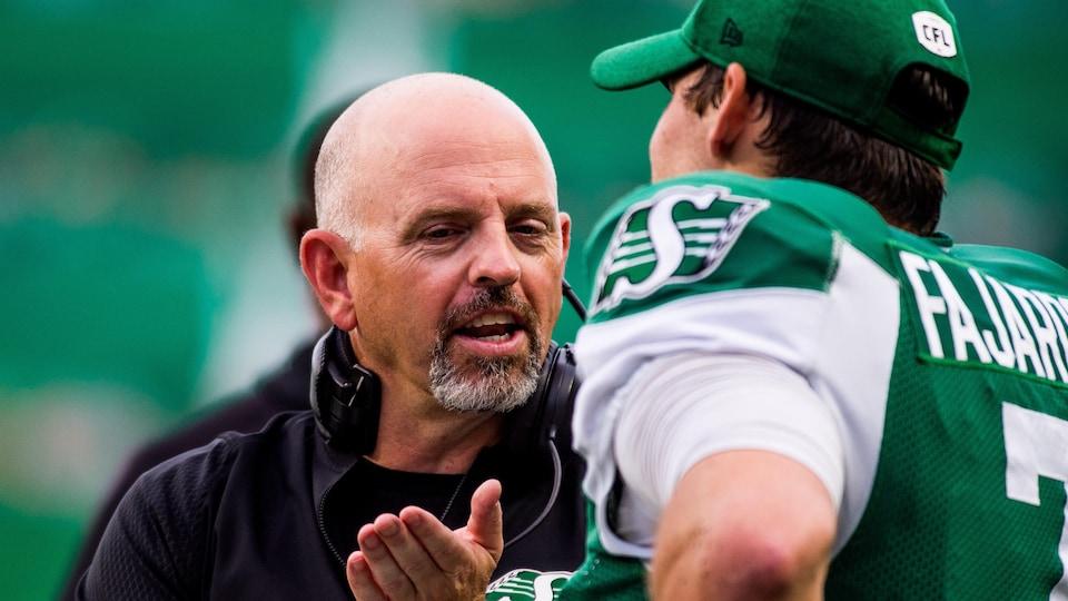 L'entraîneur-chef Craig Dickenson en conversation avec son quart-arrière Cody Fajardo.
