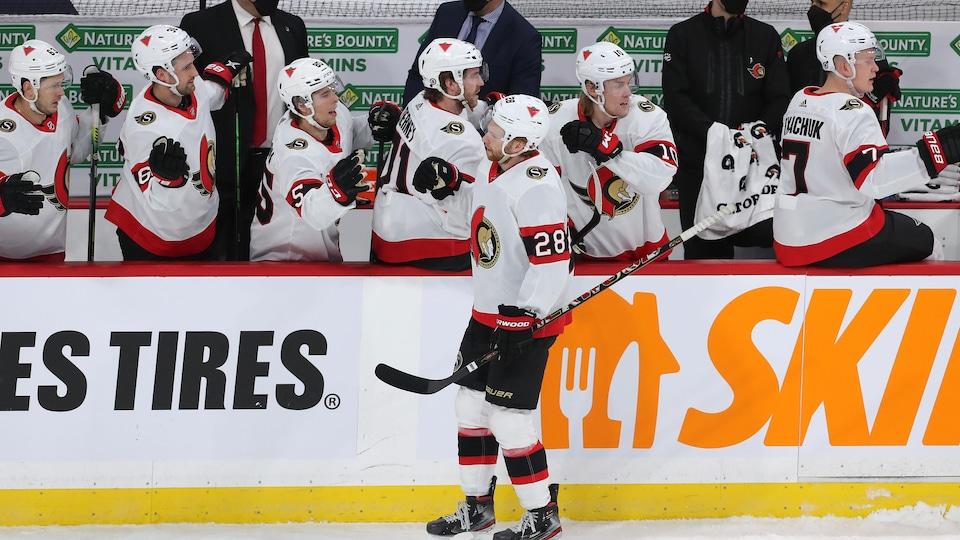 Des joueurs de hockey sont au banc de leur équipe et célèbrent un but avec leur coéquipier.