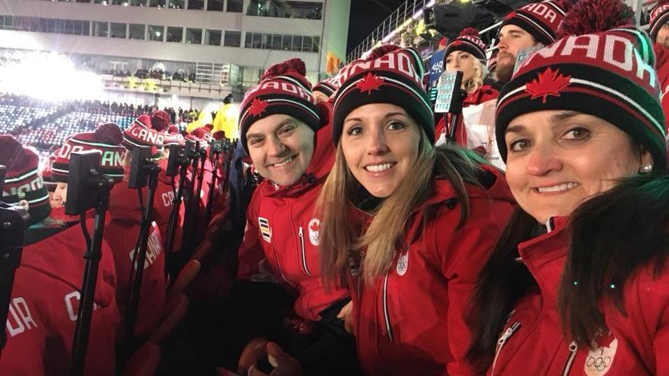 Homme et 2 femmes portant des tuques Canada et souriants à la caméra,