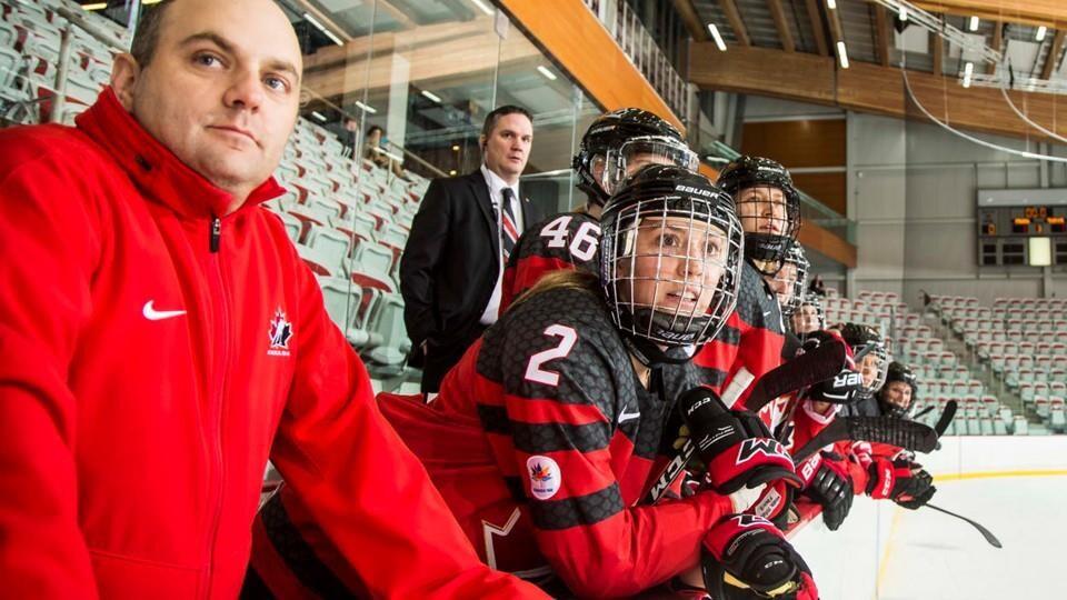 Serge LeBlanc sur le banc à côté des joueuses de hockey.
