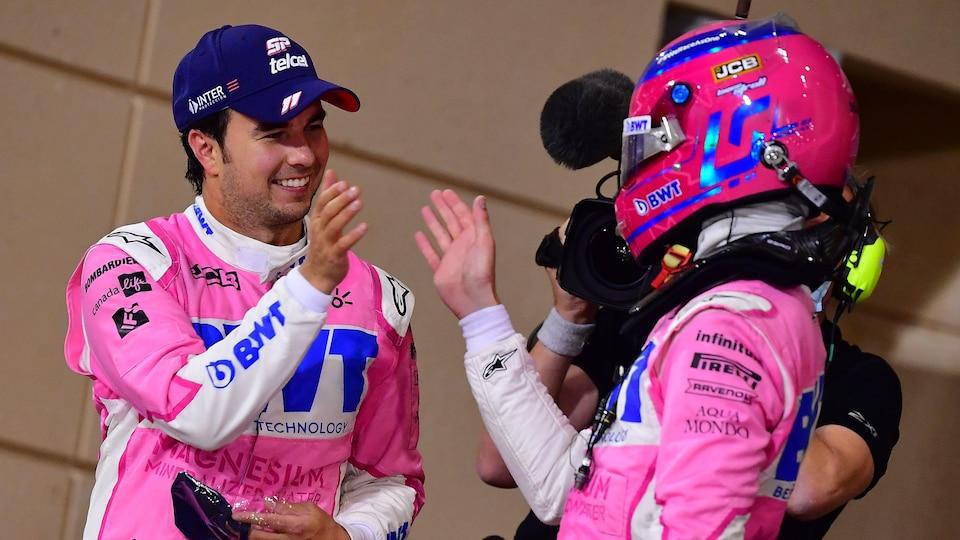 Deux pilotes de course se tapent la main pour se féliciter.