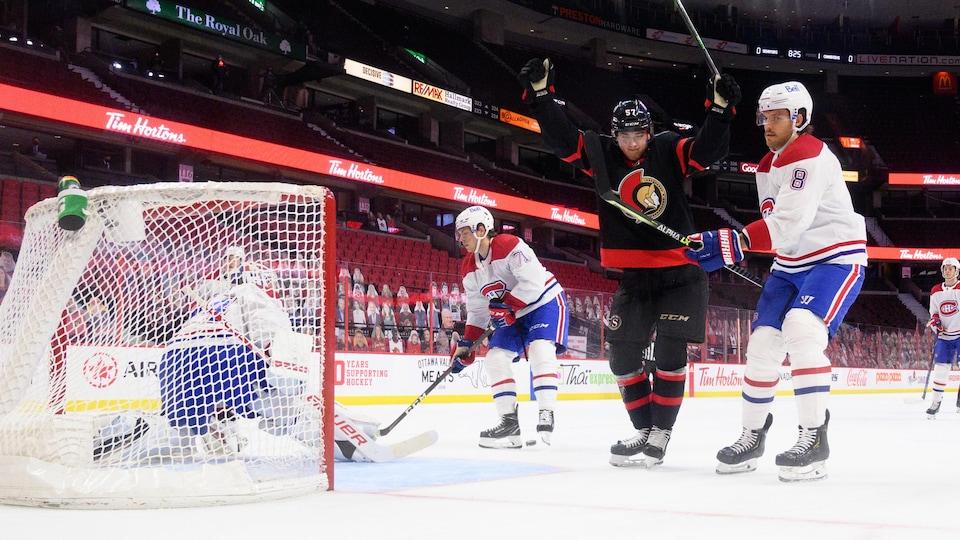 Un joueur de hockey célèbre, bras dans les airs, le premier but de sa carrière.