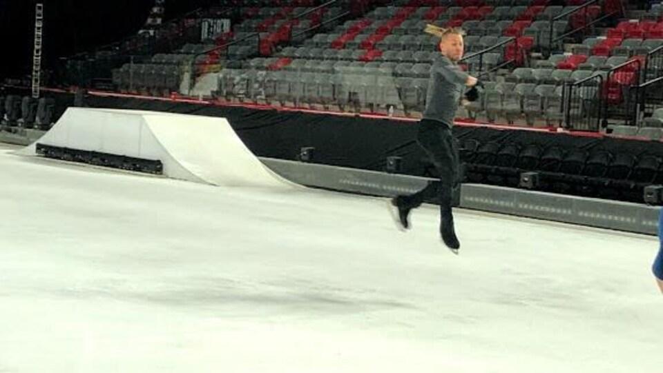 Il saute en tournant sur lui-même sur la patinoire.