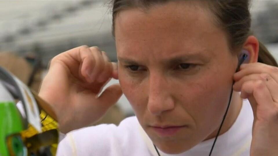 Elle met des écouteurs dans ses oreilles.