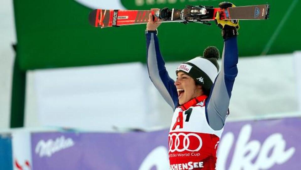 Elle brandit ses skis au-dessus de sa tête en signe de victoire.