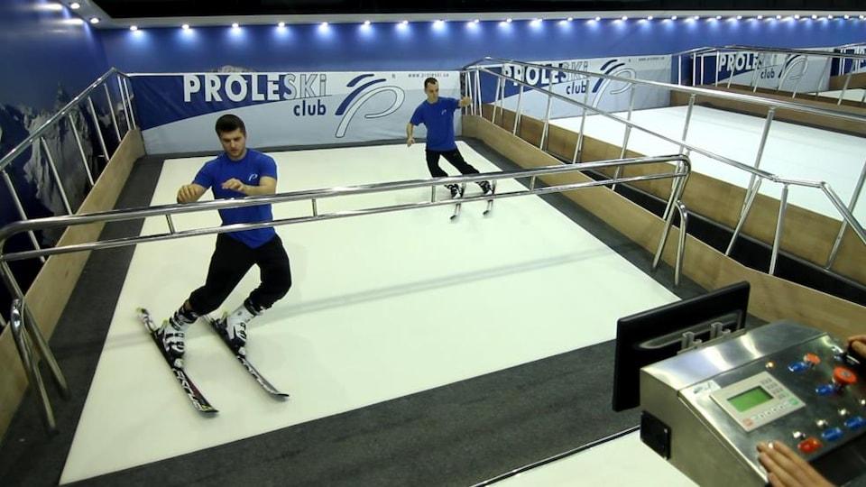 Des hommes s'entraînent au ski sur un simulateur.
