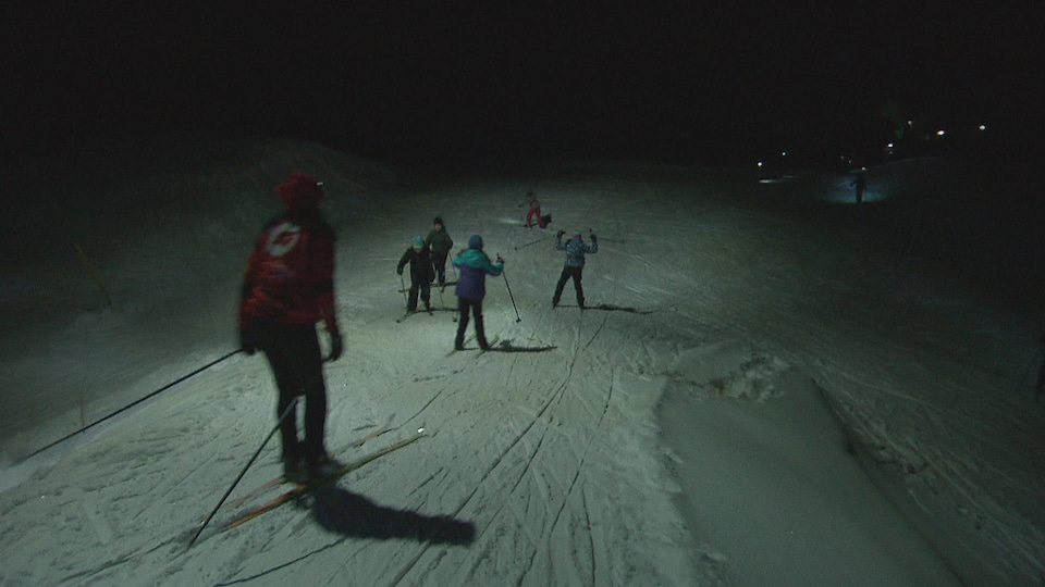 Des skieurs de fond dévalent une pente le soir.