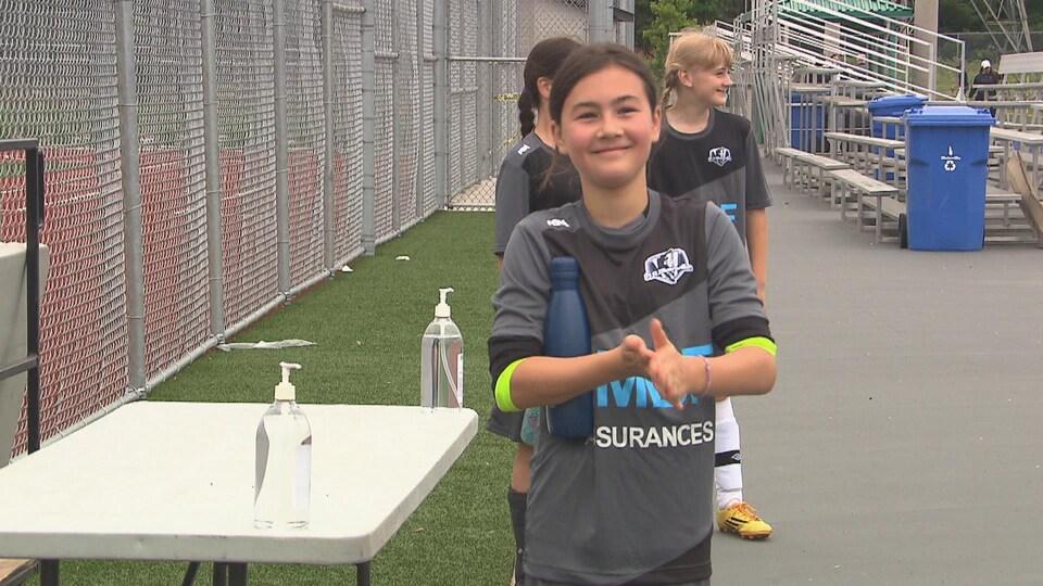 Une jeune joueuse de soccer se lave les mains avant d'entrer sur le terrain.