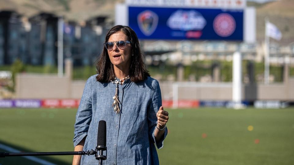 Elle s'adresse aux médias devant un terrain de soccer.