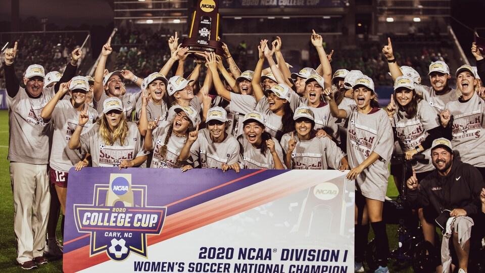Les membres de l'équipe et du personnel célèbrent leur victoire derrière une bannière qui souligne leur championnat.