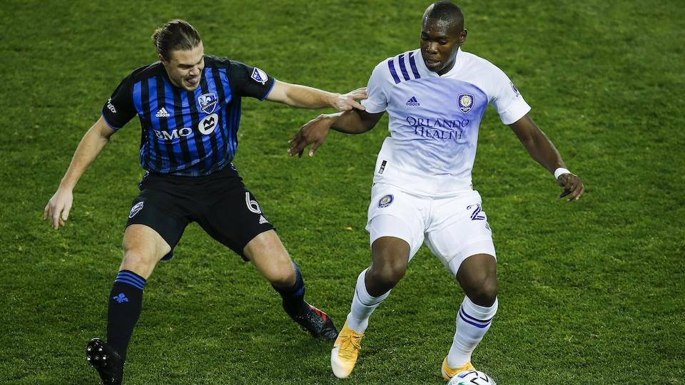 Deux joueurs de soccer bataillent pour le ballon.