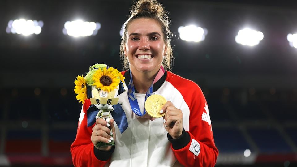 Une jeune femme montre sa médaille d'or qu'elle tient dans la main gauche et un bouquet de fleurs dans la main droite. On voit d'énormes lumières derrière elle.