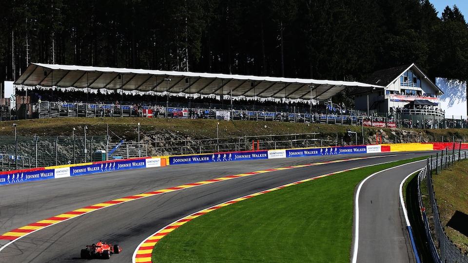 Vue générale de la montée du Raidillon à Spa-Francorchamps, une voiture négocie la grande courbe.