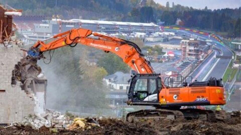 Une pelleteuse détruit un mur près du circuit de Spa-Francorchamps. On voit les installations du Grand Prix de Belgique de F1 au loin.