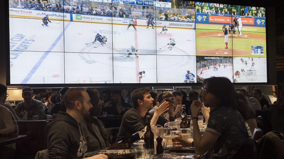 Des partisans discutent autour d'une table dans un bar pendant que des événements sportifs sont diffusés sur un écran géant.