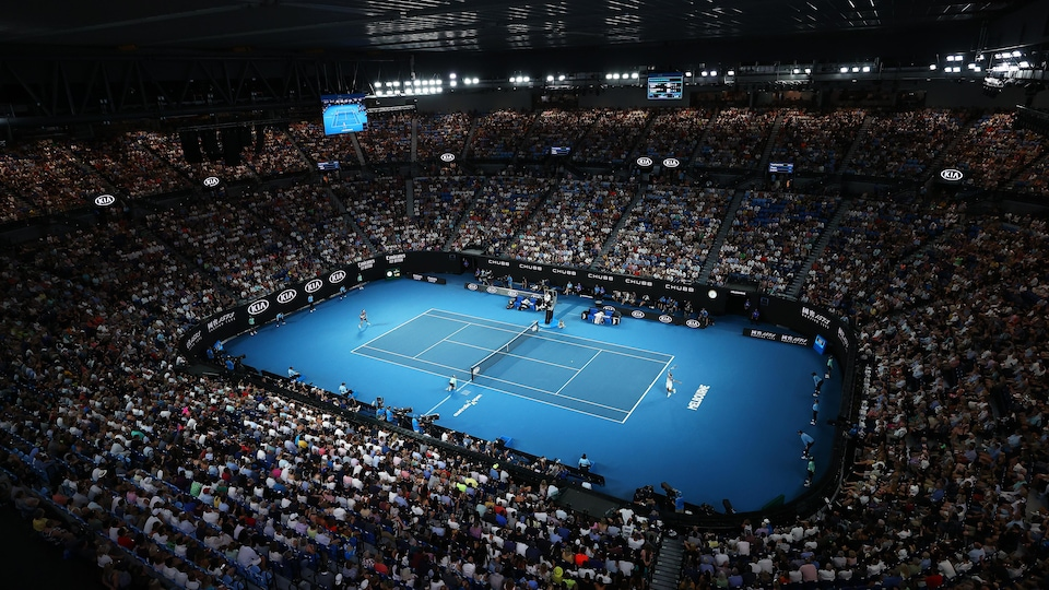Un stade de tennis rempli pendant un match.