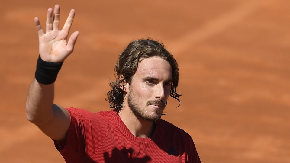 Il salue la foule de la main droite.