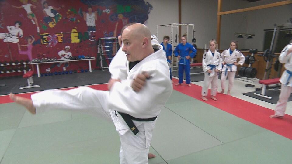 Homme en kimono, jambe en l'air, s'apprête à faire basculer un adversaire.
