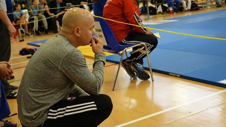 Homme chauve accroupi regardant des matchs de judo.