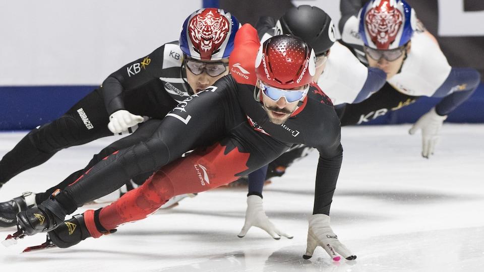 Il prend un virage, une main sur la glace, devant trois adversaires.